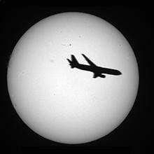 太陽の前を通過する飛行機