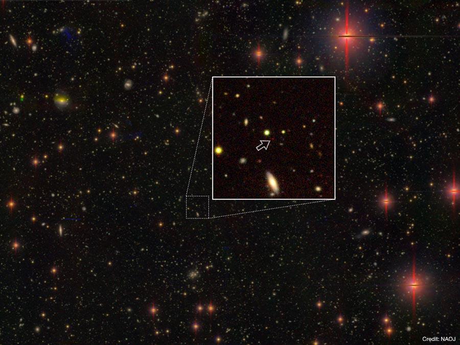 発見された巨大ブラックホール。矢印の先にある赤い天体で、地球からの距離は130.5億光年。すばる望遠鏡の超広視野主焦点カメラHSCによる探査観測で得られた画像。